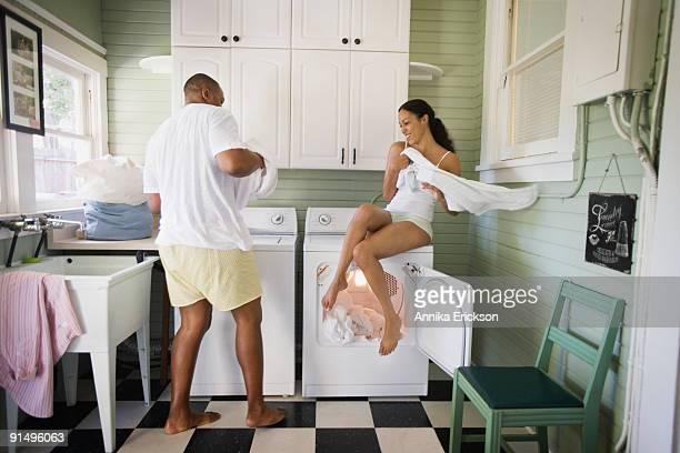 Playful couple folding laundry