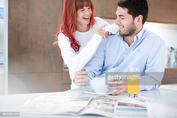 Playful couple in kitchen having breakfast