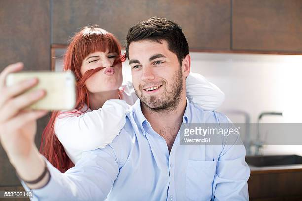 Playful couple in kitchen taking a selfie