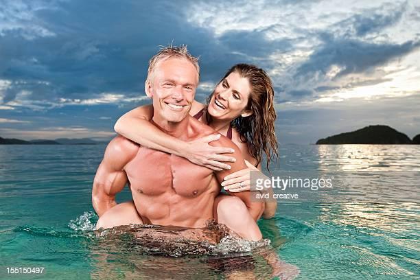 Spielerische Paar im Ozean bei Sonnenuntergang