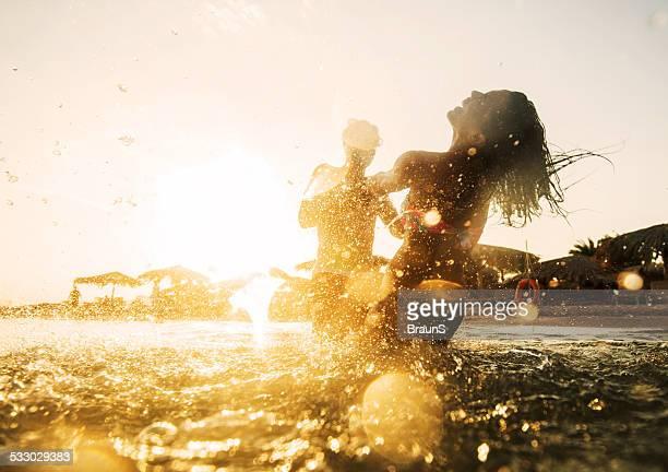couple s'amuser dans la mer au coucher du soleil.