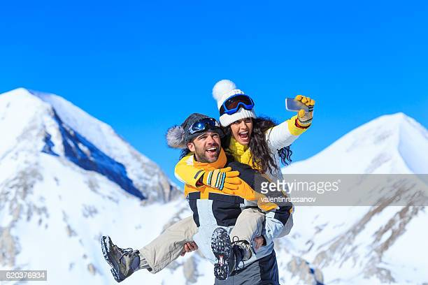 Playful couple making selfie on top snow mountain