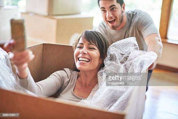 Playful couple moving house sitting in a box taking a selfie