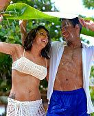 Playful couple underneath banana leaf on rainy beach