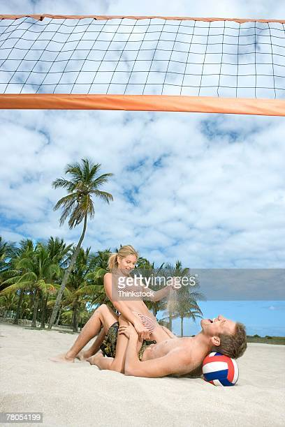 Playful couple wrestling on beach