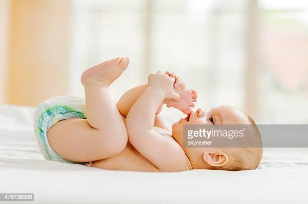 Juguetón Monada bebé acostado en la cama.