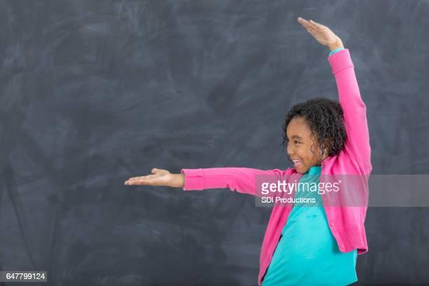 Playful elementary schoolgirl gestures in front of chalkboard