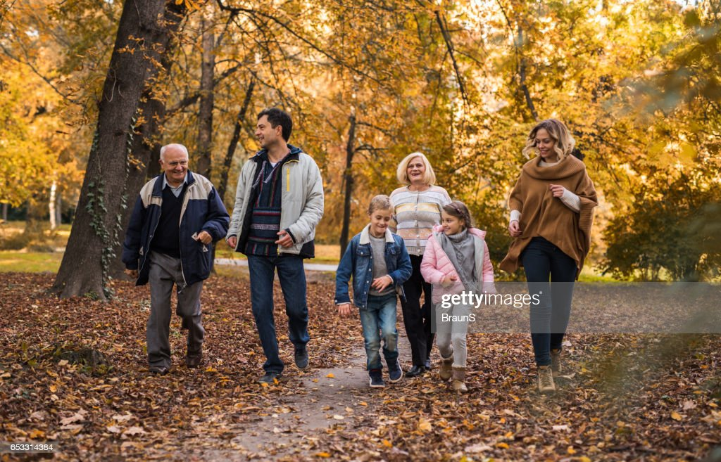 Playful extended family running together in the park. : Stock Photo