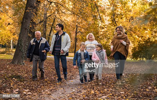 Playful extended family running together in the park. : Photo
