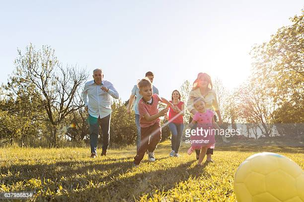 Playful extended family running towards the ball in nature.