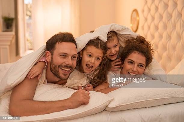 Playful family covered with duvet having fun in bedroom.