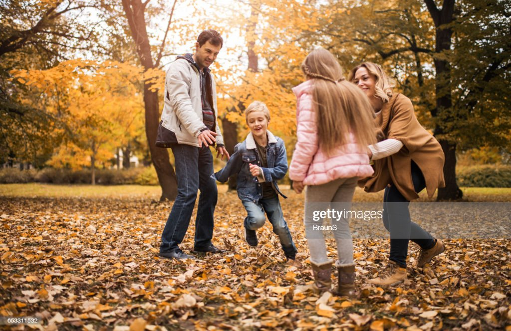 Playful family having fun during an autumn day in nature. : Stock Photo