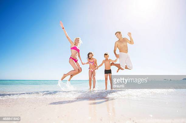 Playful family jumping in the sea and having fun.