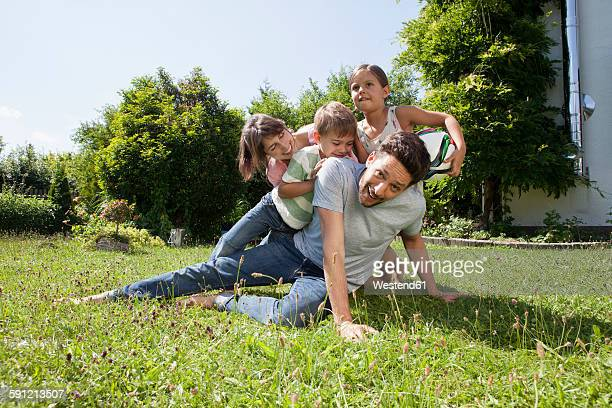 Playful family of four in garden