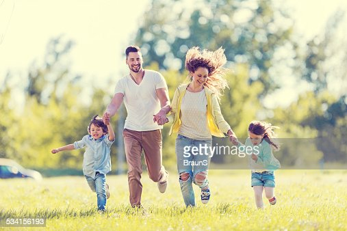 Playful family running outdoors.