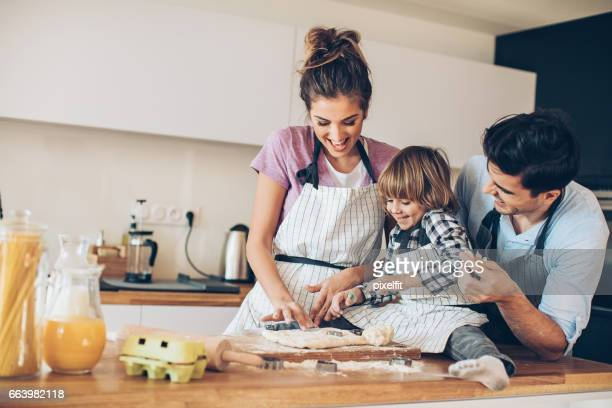 Juguetona familia con niño pequeño preparar galletas