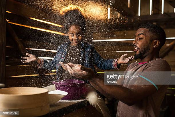 Playful father and daughter having fun with flour in mill.