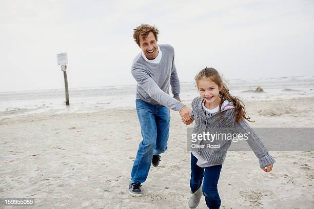 Playful father and daughter on the beach
