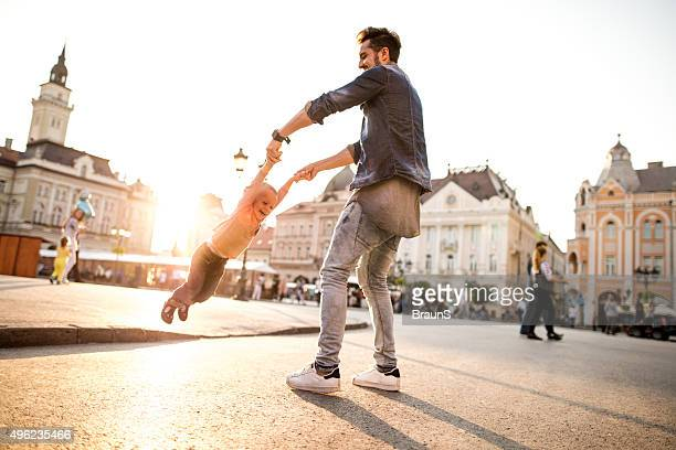 Playful father and son spinning in the city at sunset.
