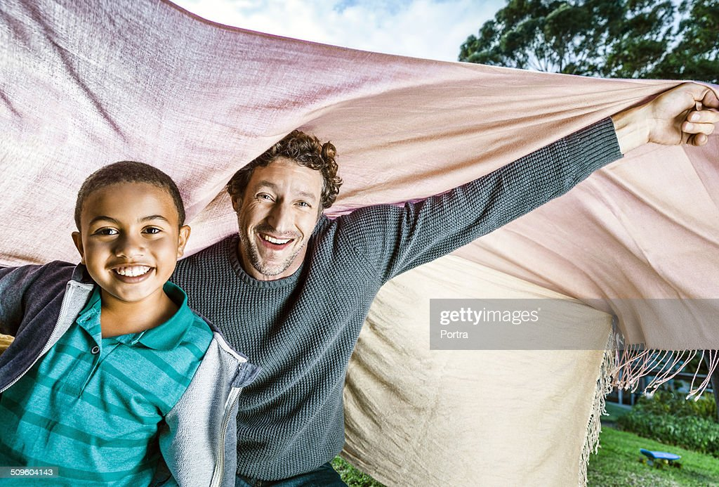 Playful father and son under blanket