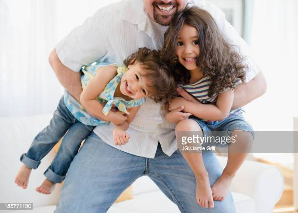 Playful father carrying daughters