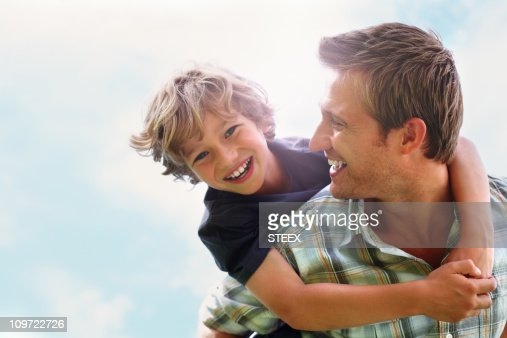 Playful father giving his son piggy back ride against sky : Stock Photo
