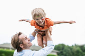 Playful father lifting injured son against clear sky