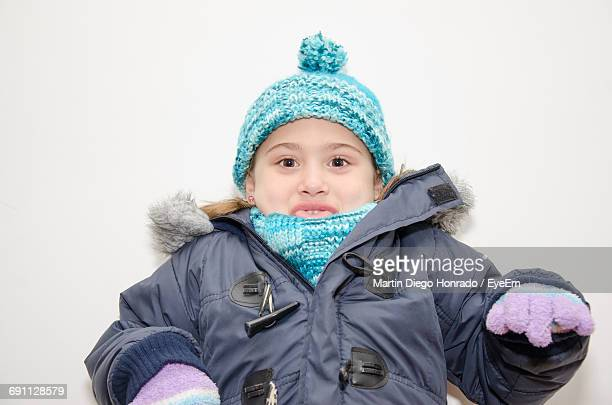 Playful Girl In Warm Clothes Sticking Out Tongue Against White Background