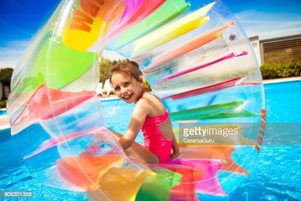 Playful Girl Inside The Water Wheel Floating On The Water In The Swimming Pool