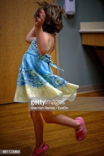 Playful Girl Jumping On Floor At Home