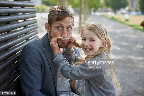 Playful girl with father on bench