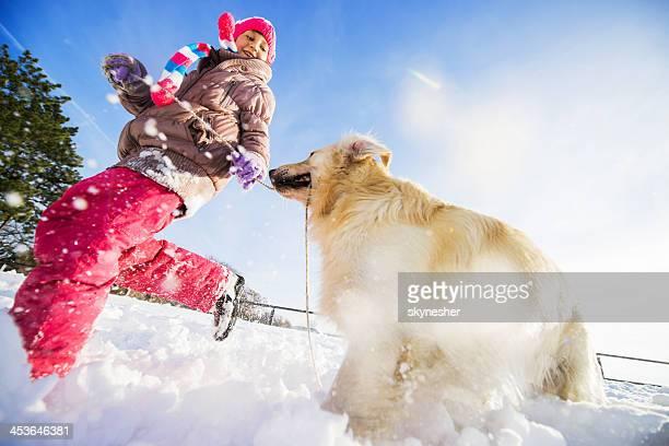 Verspielte Mädchen mit Ihrem Hund im winter.