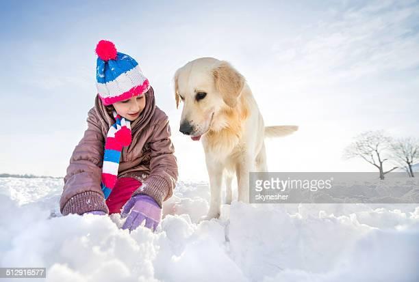 Verspielte Mädchen mit Ihrem Hund im Schnee genießen.