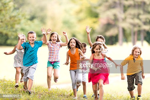 Playful group of kids running in the park.