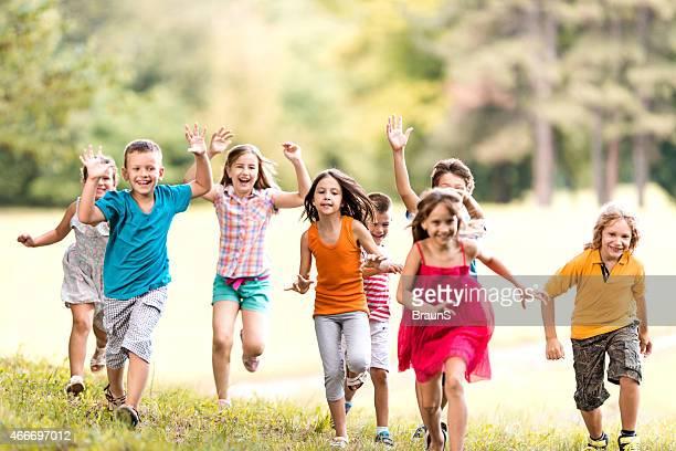 Brincalhão grupo de crianças a correr no parque.