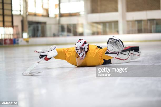 Playful ice hockey player sliding on his stomach at rink.