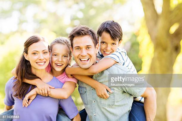 Playful Kids Enjoying Piggyback Ride On Parents