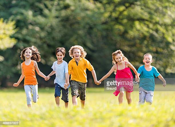 Playful kids running outdoors while holding hands.
