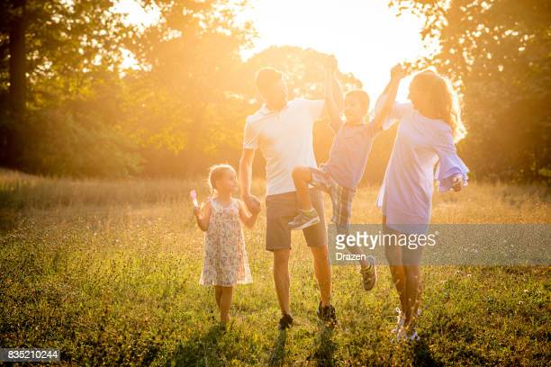 Playful kids with parents in nature