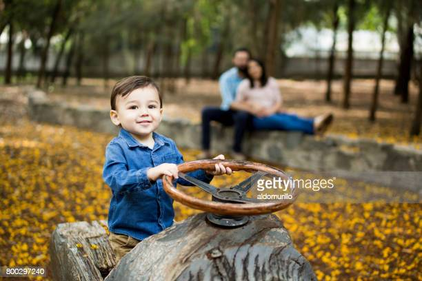 Playful little boy with steering wheel and smiling at camera