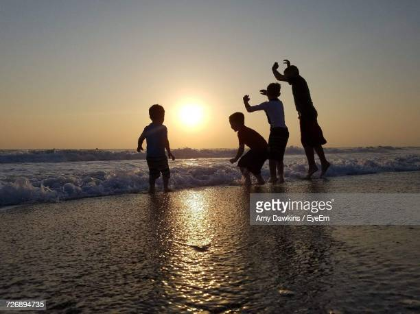 Playful Male Friends Standing On Shore At Beach During Sunset