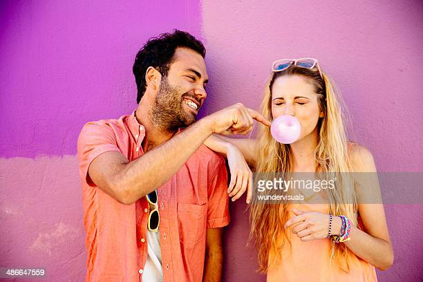 Playful man popping chewing gum bubble girl