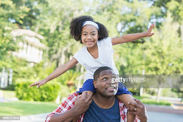 Playful mixed race girl sitting on father's shoulders