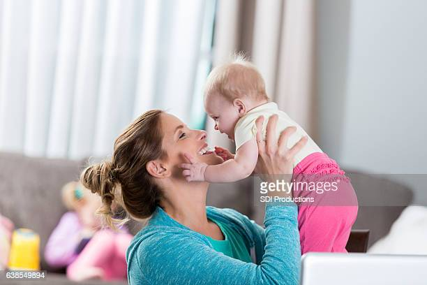 Playful mom holds up beautiful baby girl