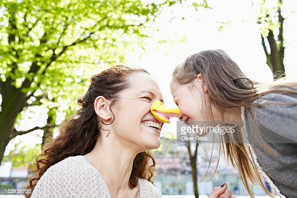 Playful mother and daughter with false nose