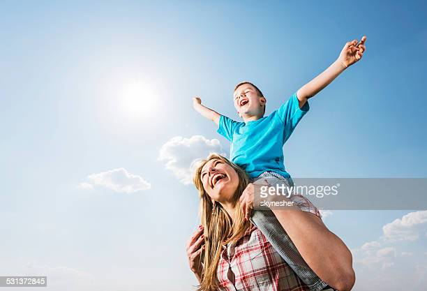 Playful mother and son against the sky.