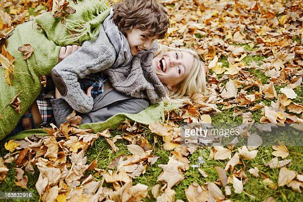 Playful mother and son in autumnal park