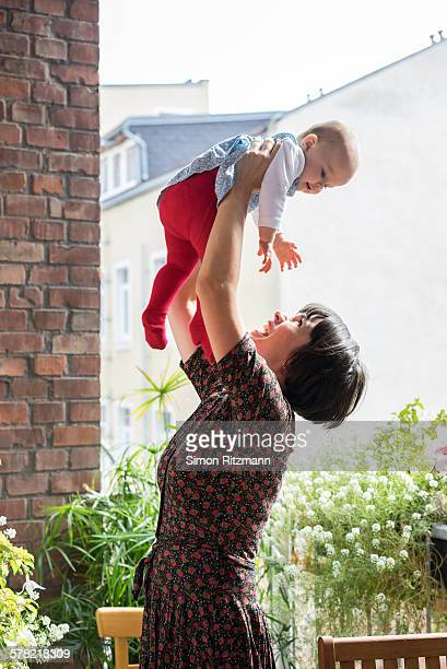 Playful mother lifting baby daughter overhead.