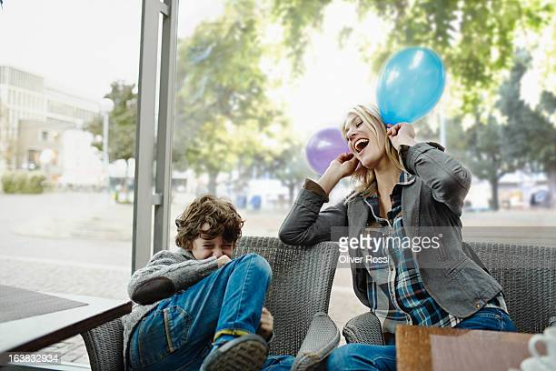 Playful mother with balloons looking at son