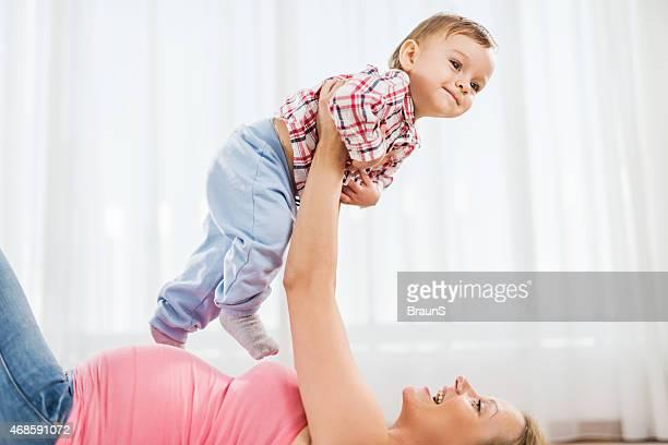 Jolie femme enceinte mère et son petit fils s'amuser ensemble.